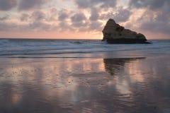 在海边沙滩的美好的五颜六色的日落与在prara da rocha隔绝的反射的峭壁 免版税库存照片