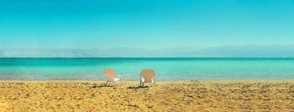 在海边的两张白色海滩睡椅 复制空间 夏天、假日和旅行概念 钞票 库存图片