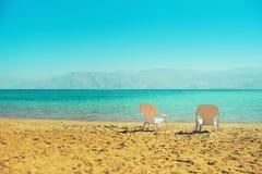 在海边的两张白色海滩睡椅 复制空间 夏天、假日和旅行概念 库存图片