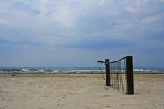 在海边的沙子放弃的生锈的被自毁的篱芭片断  免版税库存照片