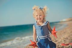 在海边的逗人喜爱的女孩与在蓝色礼服的两个海星 库存照片