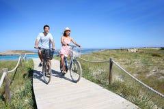 在海边的年轻夫妇骑马自行车 库存照片