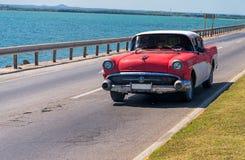 在海边高速公路的经典美国汽车 免版税库存图片