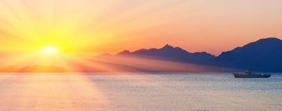 在海运和山的日落 免版税库存照片