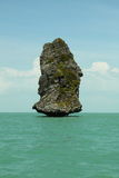 在海运和美丽的云彩之中的大岩石 图库摄影