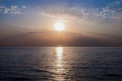 在海运展望期的日出 明亮的太阳从水表面,早晨天空被反射 免版税库存照片