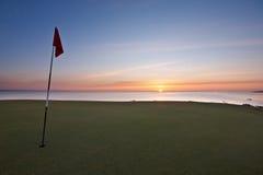 在海运日出的高尔夫球绿色 库存图片