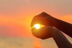 在海运日落 太阳在儿童` s手上 库存照片
