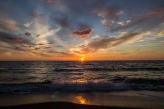 在海运的日落 在天空的明亮的太阳 波浪 免版税库存图片