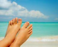 在海运背景的妇女的赤脚 免版税库存照片