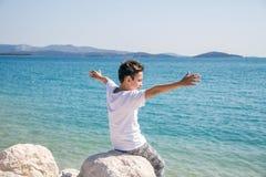 在海附近的一个愉快的男孩有宽胳膊的 免版税库存图片
