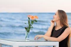 在海附近的一名美丽的妇女蓝天背景的在夏天 华美的时髦的少妇在蓝色盐水湖附近休息 免版税库存图片