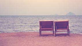 在海附近的两张海滩睡椅与很远山的日落的 免版税库存照片