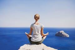 在海附近的少妇实践的瑜伽 免版税库存照片