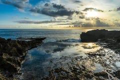 在海附近的岩石 在水池反映的日落天空 免版税图库摄影