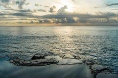 在海附近的岩石 在水池反映的日落天空 库存图片