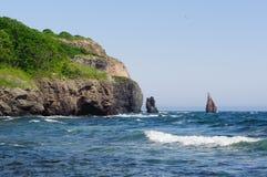 在海附近的绿色岩石 免版税库存照片