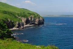 在海附近的绿色岩石 库存图片