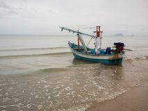 在海领带的乌贼渔船与船锚在多云早晨天,有海背景和海滩前景 免版税库存照片