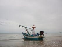 在海领带的乌贼渔船与船锚在多云早晨天,有海背景和海滩前景 库存照片
