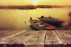 在海风景和渔船前面的木委员会 免版税库存照片