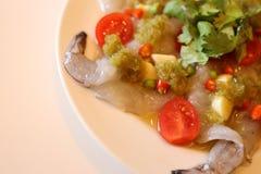 在海鲜调味料浸泡的未加工的虾供食由大蒜和红辣椒 图库摄影