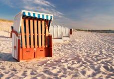 在海滩、波罗的海和软的沙子的被顶房顶的柳条海滩睡椅 免版税库存图片