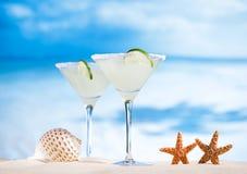 在海滩、蓝色海和天空的玛格丽塔鸡尾酒 免版税库存图片