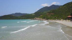 在海滩上的低飞行,在美丽的海滩礁石和蓝色海洋鸟瞰图  股票录像