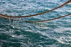 在海水上的老被撕毁的固艇索具 免版税库存图片