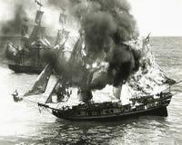 在海洋中间的灼烧的小船 免版税库存照片