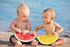 在海滩亚裔女婴和白男孩吃果子 免版税库存图片