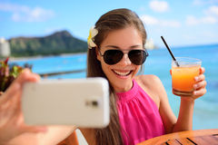 在海滩假期酒吧的Selfie妇女饮用的饮料 免版税图库摄影