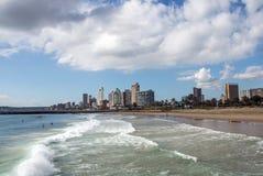 在海滩前的多云蓝天反对城市地平线 免版税图库摄影