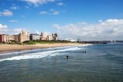 在海滩前的多云蓝天反对城市地平线 图库摄影