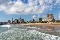 在海滩前的多云蓝天反对城市地平线 免版税库存图片
