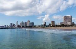 在海滩前的多云蓝天反对城市地平线 库存图片