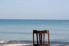 在海滩前的老木椅子 库存照片