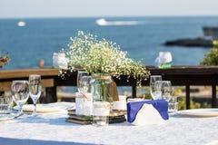 在海滩前面的典雅的夏天婚礼桌 库存照片