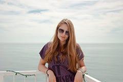 在海洋前面的妇女佩带的太阳镜 免版税图库摄影
