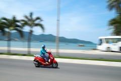 在海滩前面的无法认出的motobike司机在芽庄市,越南附近 夺取在行动,被弄脏 使用a 免版税库存图片