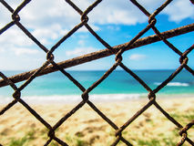在海滩前面的生锈的链节篱芭 库存照片