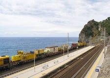 在海洋前面的黄色火车在Corniglia,意大利 库存图片