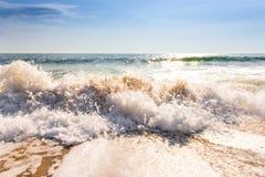 在海水以后日出和飞溅铺沙海海滩和蓝天 免版税库存照片