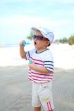 在海滩吹的泡影的孩子 免版税库存图片