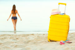 在海滩和女孩的黄色手提箱走入Th的海 免版税图库摄影