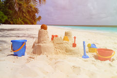 在海滩和孩子玩具的沙子城堡 免版税库存图片