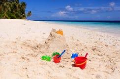在海滩和孩子玩具的沙子城堡 图库摄影