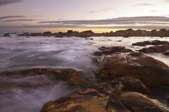 在海洋和岩石的太阳设置 免版税库存照片