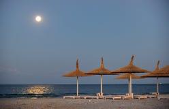 在海滩和月亮的遮阳伞 免版税库存照片